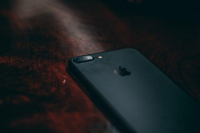 Un iPhone noir sur un coin de table.